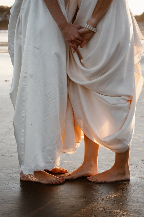 Crop anonymous barefoot couple wearing loose white clothes holding hands gently and standing close on wet sandy beach at sunset