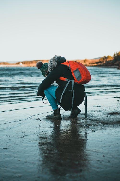 Anonymous photographer shooting sea on sandy shore