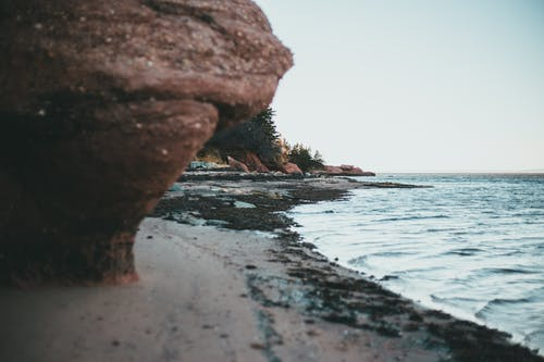 Sandy seashore surrounded by rocky cliffs