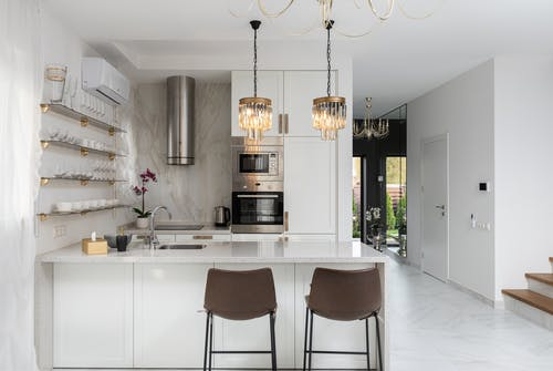 Interior of contemporary kitchen with modern appliances and chairs at white counter near  wall with shelves in spacious apartment near stairs