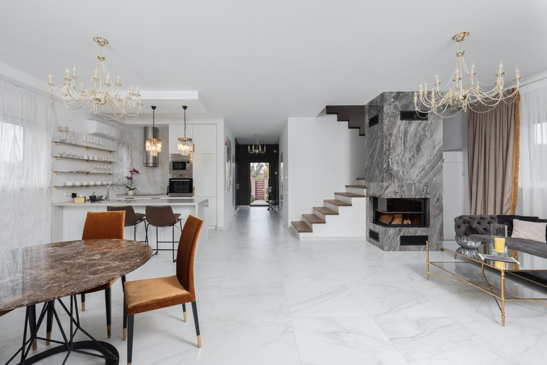 Stylish apartment with chairs at table placed near white kitchen counter in room with couch and side table near fireplace at staircase
