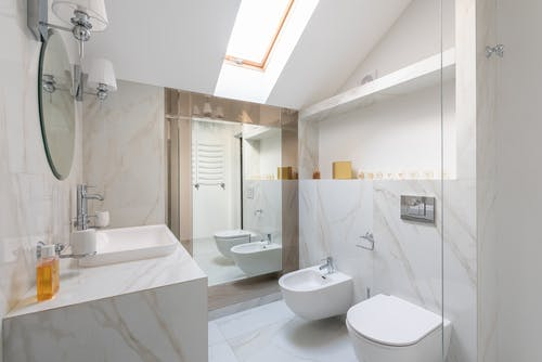 Interior of light restroom with sink on marble cupboard against white bidets and mirror on wall and window on ceiling