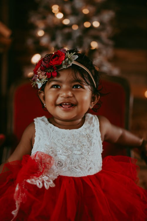 Joyful little Asian girl in elegant dress and headband sitting on comfy chair and looking away with happy smile