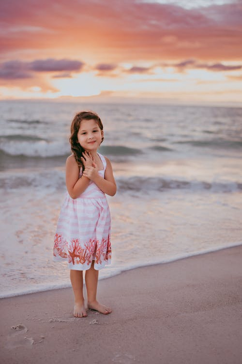 Pretty barefoot girl standing on seashore at sunset
