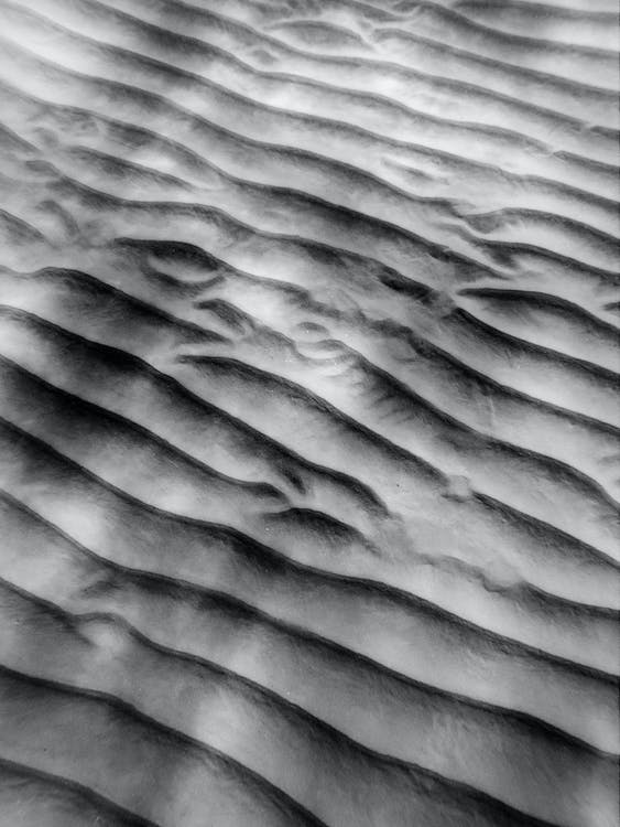 Textured background of sandy shore with ribbed surface
