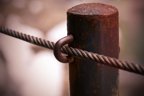 A Close-up Shot of a Rusted Fence Pole with Steel Cable
