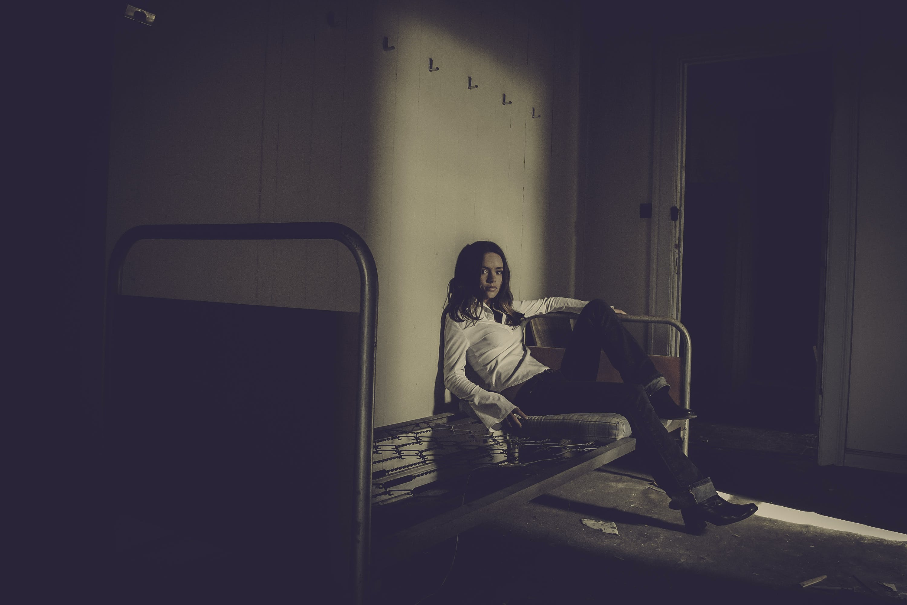 Woman Sitting on Bed Inside Empty Room