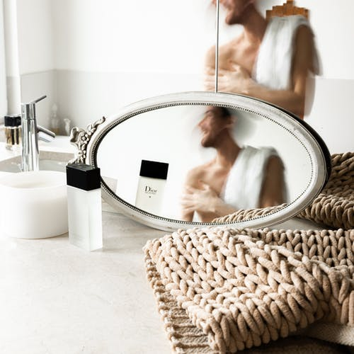 Reflection of unrecognizable young shirtless male in misted mirrors after taking shower in modern light bathroom