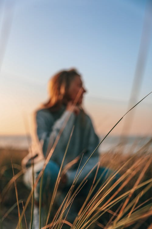 Unrecognizable woman recreating in meadow near seashore at sundown