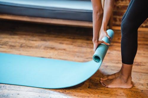 Crop unrecognizable ethnic woman in leggings preparing yoga mat for training in studio in daytime