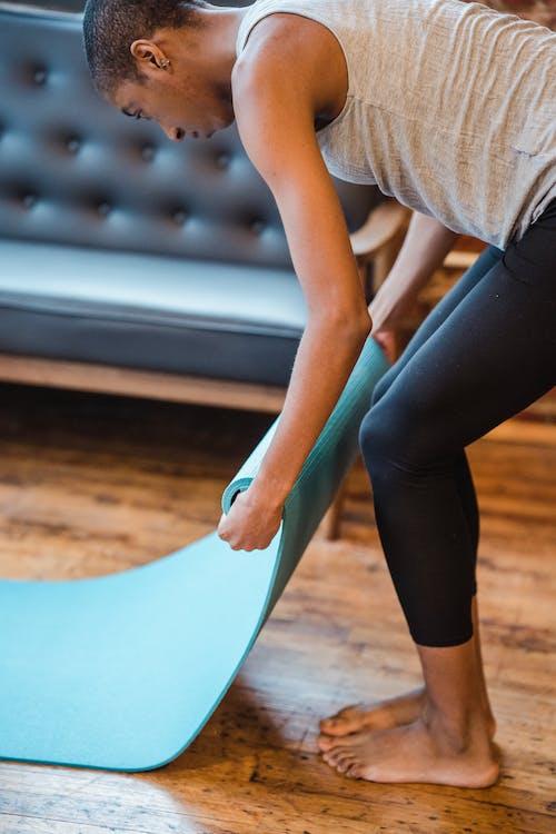 Sportive black woman preparing yoga mat for training in studio