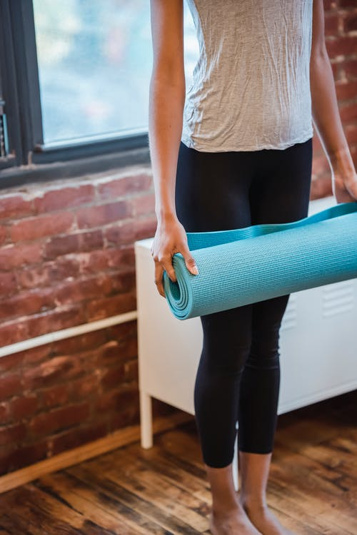 Crop anonymous person in leggings and t shirt standing with yoga mat in hands against window in studio in daytime