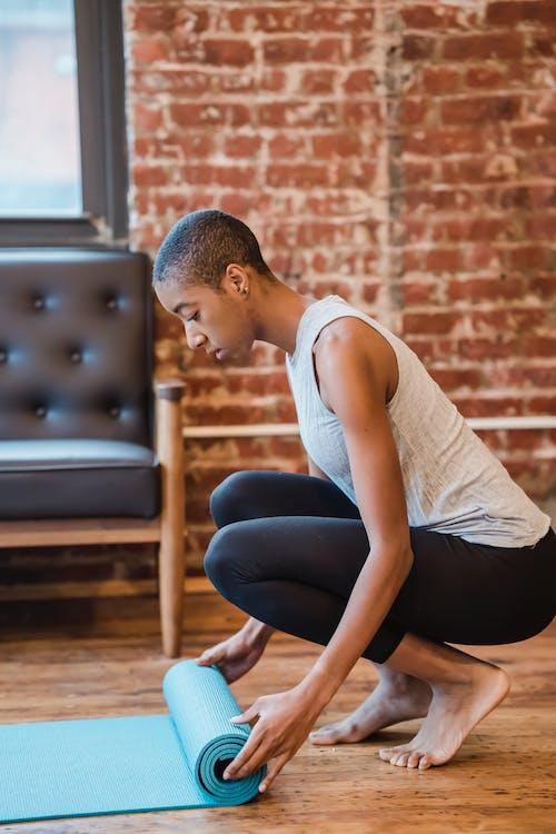 Black woman preparing sports mat for training