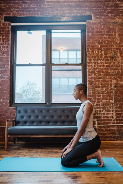 Side view full body of concentrated African American female sitting on knees in Diamond Pose during meditation