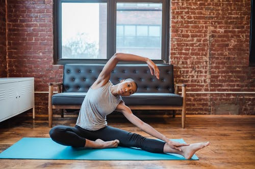 Full body of slim African American graceful female doing lateral bend exercise sitting on sports mat during training