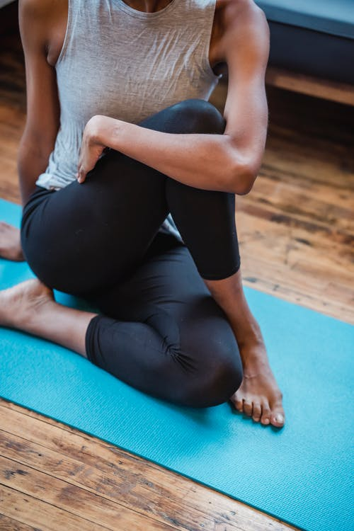 Black woman practicing Ardha Matsyendrasana during yoga training