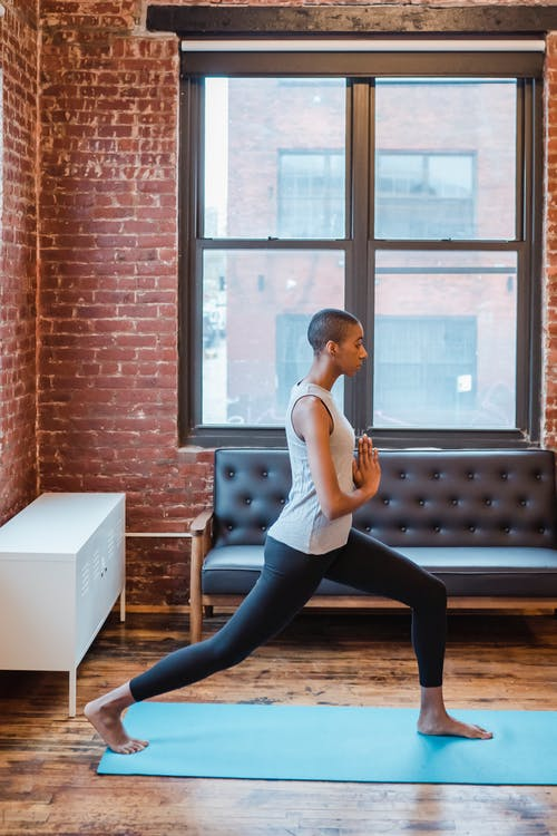 Full body side view of sportive African American female in activewear practicing anjaneyasana posture during yoga training on mat at home