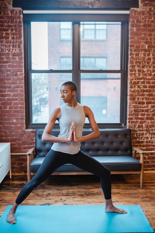 Sportive African American female in activewear practicing crescent lunge with folded hands during yoga training in light room with window