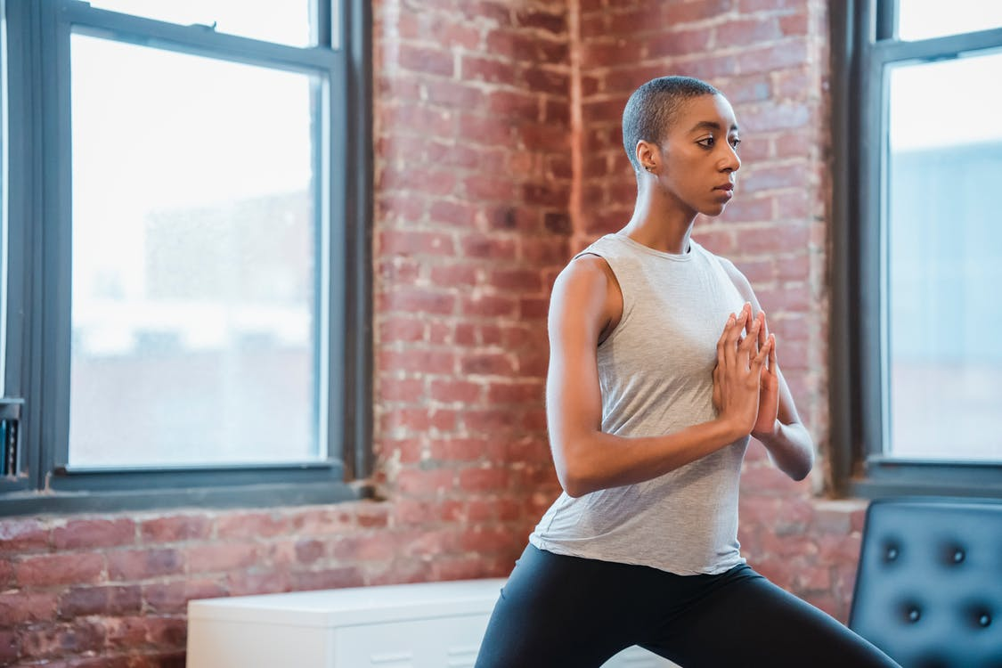 Side view of sporty African American female with short hair doing crescent lunge with folded hands while practicing yoga at home