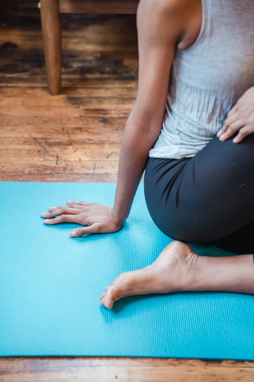 Faceless sportive barefoot African American female practicing half lord of the fishes asana while sitting on mat during yoga workout at home