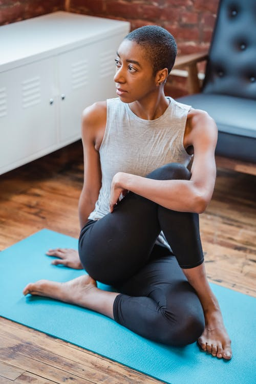 Active African American female exercising Half Lord of the Fishes asana while sitting on mat during yoga training on mat