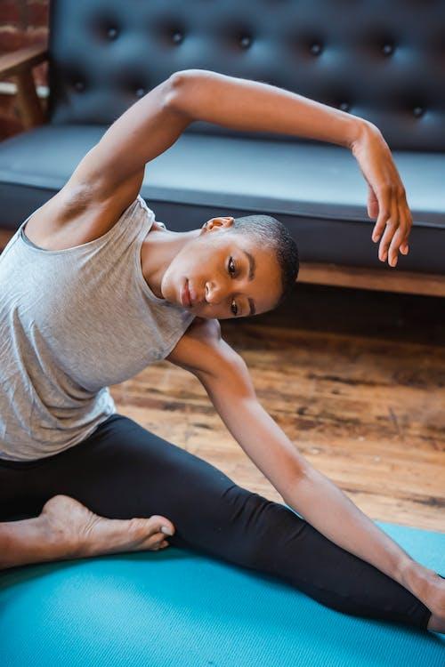 Active black woman doing revolved head to knee asana