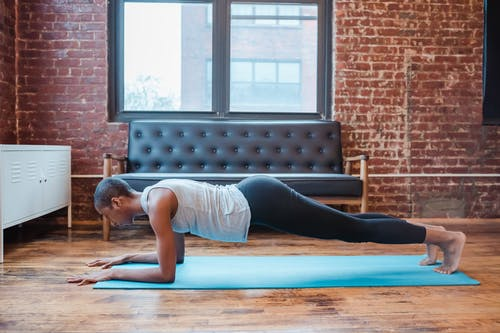 Determined black woman doing forearm plank at home