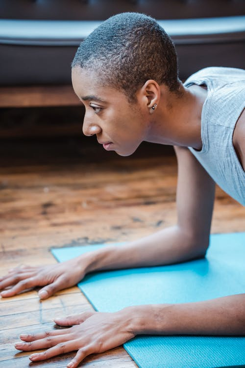 Side view of sportive African American female with short hair practicing Phalakasana posture on mat during intense yoga workout