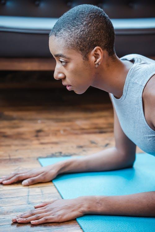 Focused black sportswoman exercising Phalakasana posture