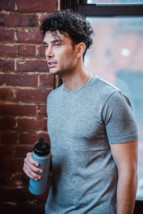 Man in Gray Crew Neck T-shirt Holding Black and Gray Tumbler