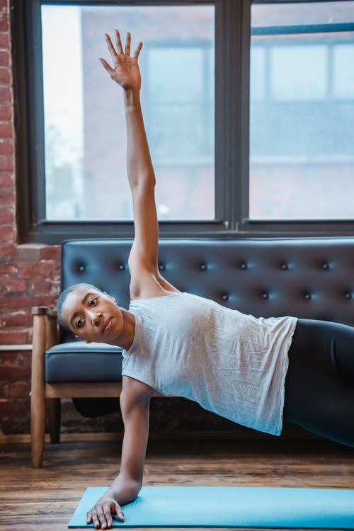 Sportive African American female in activewear doing side plank with raised arm on mat during yoga workout at home with window
