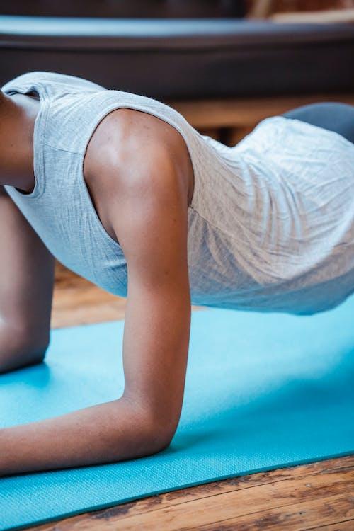 Crop black woman doing Phalakasana exercise