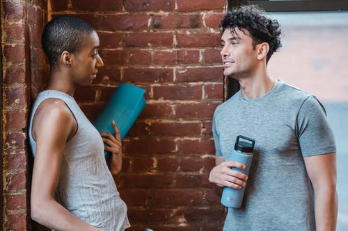 Side view of cheerful African American woman with rolled mat and fit man in sportswear looking at each other while chatting during break