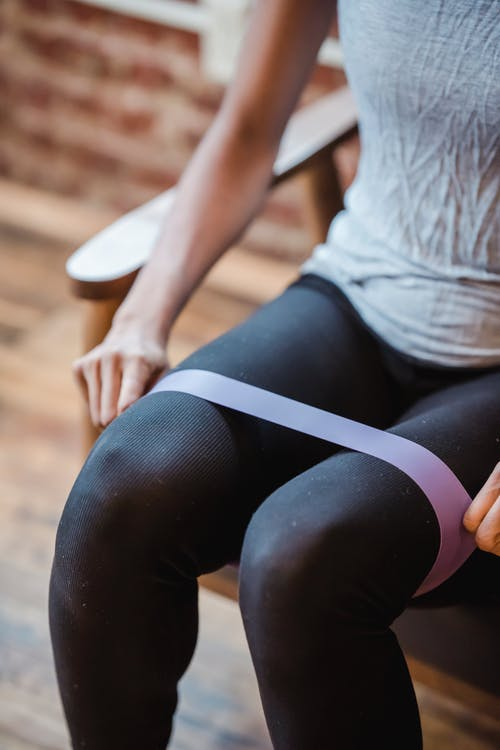 Crop sportswoman exercising with resistance band