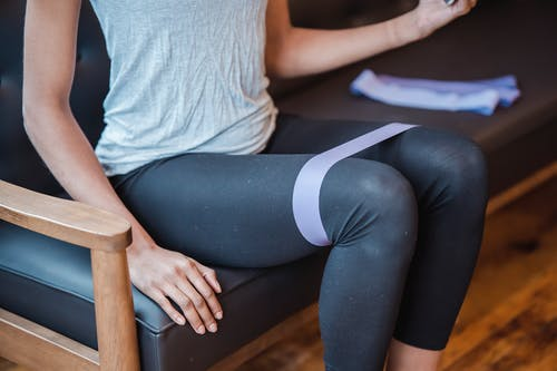 Faceless slim strong female in sportswear sitting on couch while exercising with elastic resistance band on legs during intense workout