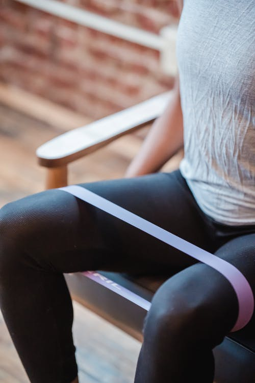 Unrecognizable sportive strong female wearing black leggings exercising with fitness expander on legs while sitting on couch on blurred background