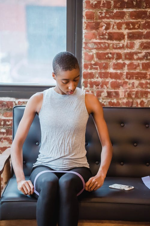 Sportive African American female exercising with fitness expander and looking at screen of cellphone while sitting on couch during training