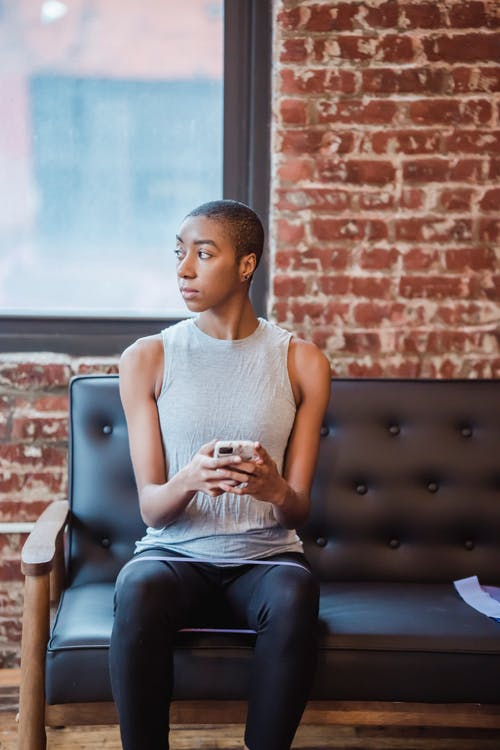Pensive African American sportive female in activewear browsing cellphone on couch and looking away during training with resistance fitness expander