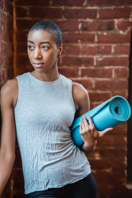 Black sportswoman with mat in gym