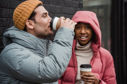 Cheerful diverse couple drinking coffee on street