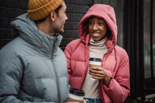 Happy diverse couple with takeaway beverages on cold day