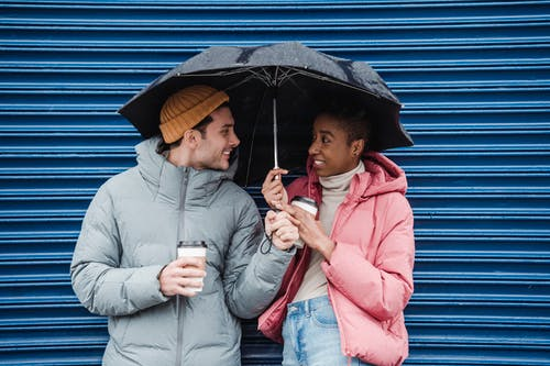 Positive multiracial couple in warm outerwear with takeaway coffee looking at each other while standing on street in rainy weather