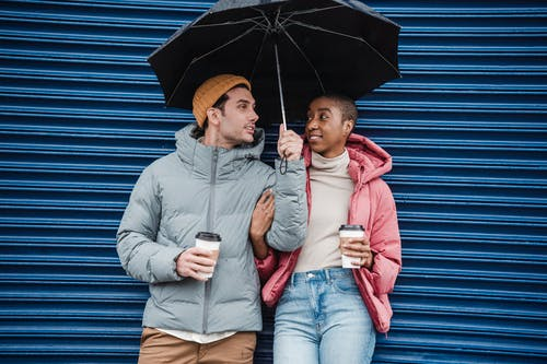 Optimistic diverse couple with takeaway coffee on street