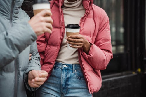 Crop couple with takeaway coffee