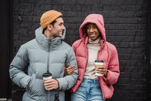 Optimistic multiethnic couple with beverages on street