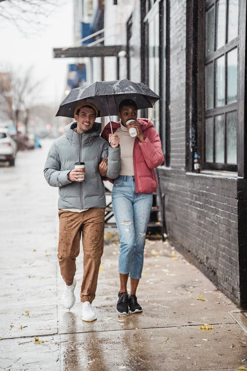 Cheerful diverse couple walking on street with coffee on rainy day