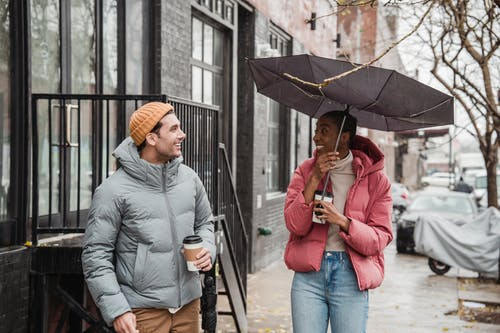 Positive African American woman with umbrella and man looking at each other while standing with takeaway coffee on rainy and windy day
