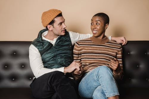 Content multiethnic couple sitting on couch