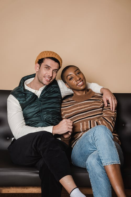 Cheerful loving multiracial couple hugging on comfortable couch and looking at camera with smile while spending time in living room