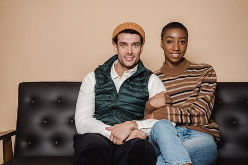 Happy multiethnic couple sitting on couch